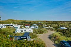 Camping site called `Kogerstrand` with big cars and camper vans in the dunes near beach onisland Texel