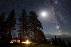 Male hiker enjoyng night camping near tourist tent at campfire under blue starry sky and Milky way stock photo