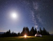 Male hiker enjoyng night camping near tourist tent at campfire under blue starry sky and Milky way. Camping site in mountain valley at night. Male hiker standing stock image