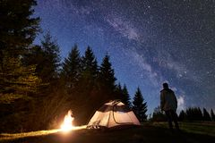 Male hiker enjoyng night camping near tourist tent at campfire under blue starry sky and Milky way stock image
