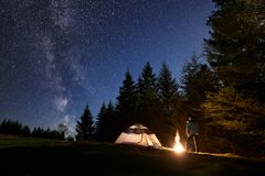 Male hiker enjoyng night camping near tourist tent at campfire under blue starry sky and Milky way royalty free stock images