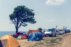 Camping site near the sea, cars and tents on the sea beach stock image