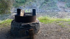 Campground firepit and river. A camping site next to a river with a fire pit Stock Image
