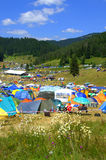 Camping site Rozhen Fair ,Bulgaria. Mountain meadow packed with tents and people relaxing at beautiful scenery of Rhodope Mountains near the popular Pamporovo royalty free stock photography