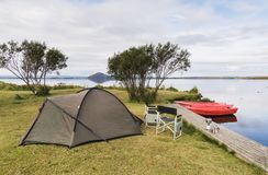Camping site with a tent, two folding chairs and boats at the coast of Myvatn lake, Iceland stock images