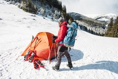Camping in the snow. Winter trekking in the mountains. Orange tent, snowshoes and trekking poles. A man with a backpack sets a tent on the snow. Extreme royalty free stock image