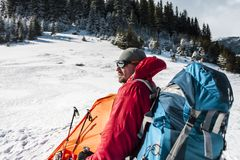 Camping in the snow. Winter trekking in the mountains. Orange tent, snowshoes and trekking poles. A man with a backpack sets a tent on the snow. Extreme stock photography