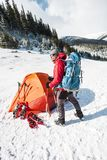 Camping in the snow. Winter trekking in the mountains. Orange tent, snowshoes and trekking poles. A man with a backpack sets a tent on the snow. Extreme stock photos