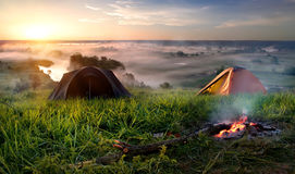 Camping in steppe. Tents and bonfire in steppe near river at sunrise Royalty Free Stock Image