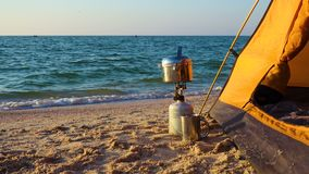 Camping stove with cooking pan near tent on a sandy sea beach at sunrise time