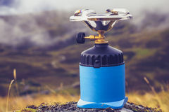 Camping stove on a rock in the mountains. Gas camping stove on a rock in the mountains with clouds in the background Stock Photo