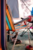 Camping sun lounger. Sun lounger with orange , blue, red and yellow stripes in a camping scene Stock Photos