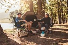 Camping supérieur de couples par un lac Images stock