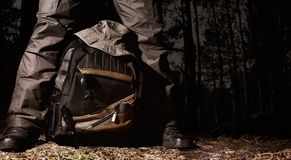 Camping tactical gear in night woods. Man in tactical outfit standing over a backpack with camping and tactical gear on night forest background Royalty Free Stock Photography