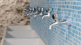 Camping taps. Taps and wash basins on blue tiles in camping Royalty Free Stock Images