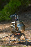 Camping teapot. Boiling on gas stove in forest royalty free stock photo