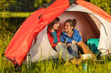 Camping teenagers sitting and embracing in tent Royalty Free Stock Photography