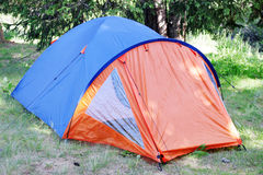 Camping Tent. In the mountains in the shadow under the trees Royalty Free Stock Images