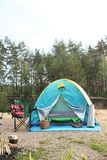 Camping tent and accessories in wilderness Stock Photos