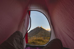 Camping with tent on the Alps. View from tent interior at sunrise, body part. Adventure and exploration, outdoor activity. Royalty Free Stock Photo