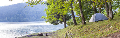 Camping tent on the bank of a lake panorama.  stock image