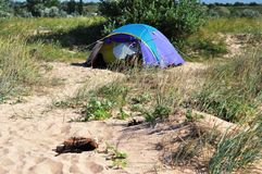 Camping tent on the beach. Blue camping tent standing on sandy shore. on the front place laying firewood for campfire royalty free stock images