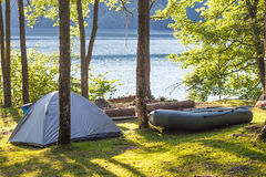 Camping tent and a boat in green forest on the bank of a lake.  royalty free stock photos