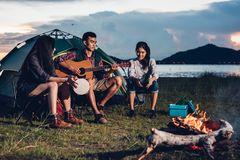 Camping tent camp in nature happy friends group night party bonfire and playing guitar together. In summer at nature forest royalty free stock photos