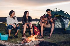 Camping tent camp in nature happy friends group night party bonfire and playing guitar together. In summer at nature forest royalty free stock photography