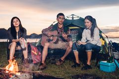 Camping tent camp in nature happy friends group night party bonfire and playing guitar together. In summer at nature forest stock photos
