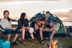 Camping tent camp in nature happy friends group night party bonfire and playing guitar together. In summer at nature forest stock images