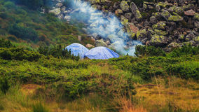 Camping tent and campfire smoke in Carpathian mountains, summertime journey. Camping tent and campfire smoke in Carpathian mountains, summertime journey Royalty Free Stock Photo