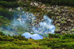 Camping tent and campfire smoke in Carpathian mountains, summertime journey. Camping tent and campfire smoke in Carpathian mountains, summertime journey Stock Images