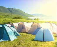 Camping tent in campground at national park. Tourists camped in the woods on the shore of the lake on the hillside stock photos