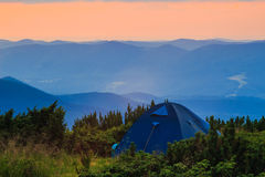 Camping tent in Carpathian mountains, sunset evening time, summertime journey. Royalty Free Stock Image