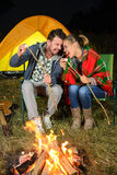 Camping. Tent camping couple romantic sitting by bonfire night countryside royalty free stock images
