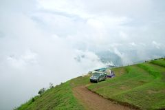 Camping tent and dark grey car on mountain peak. With view of mountain landscape, waves of fog and cloudy sky at Phu Tub Berg, Phetchabun province, Thailand stock images