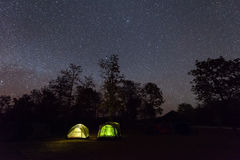 Camping tent glows under a night sky full of stars.  Royalty Free Stock Photos