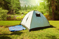 Camping tent on grass over beautiful forest Royalty Free Stock Photo