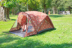 Camping tent on green grass field of forest national park Royalty Free Stock Photo