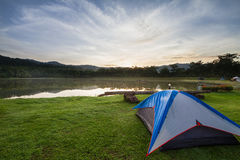 Camping tent on green grass beside lake with foggy over forest during sunrise Royalty Free Stock Images