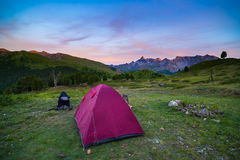 Camping with tent at high altitude on the Alps. Snowcapped mountain range and scenic colorful sky at sunset. Adventure and explora Royalty Free Stock Images