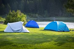 Camping tent by the lake. In green forest stock images