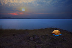 Camping tent in mountain with sun rising on sky Royalty Free Stock Images