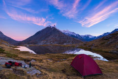 Camping with tent near high altitude lake on the Alps. Reflection of snowcapped mountain range and scenic colorful sky at sunset. Royalty Free Stock Image