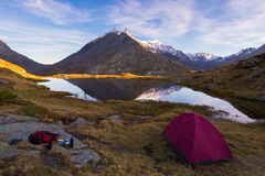 Camping with tent near high altitude lake on the Alps. Reflection of snowcapped mountain range and scenic colorful sky at sunset. Stock Photography