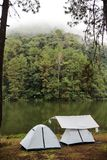 Camping tent by the river. Background stock photo