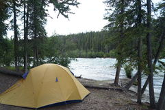 Camping. A tent beside a river Stock Image