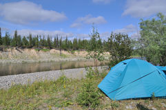 Camping tent by the river. Royalty Free Stock Images