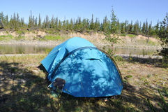 Camping tent on the shore of a mountain river. Royalty Free Stock Photos